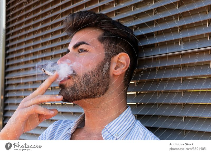 Tranquil man smoking on street smoke cigarette addict handsome city thoughtful vapor fume male building contemplate nicotine urban think relax wistful ponder