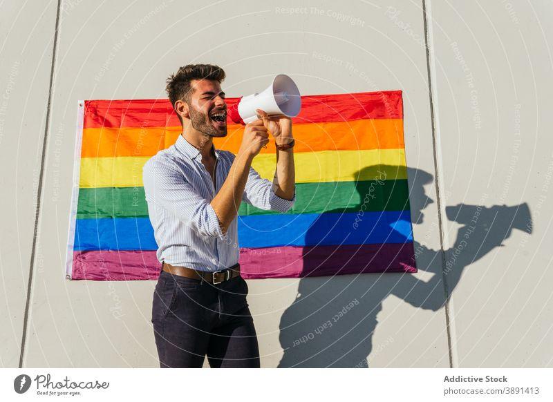 Gay man screaming in megaphone on street loudspeaker homosexual lgbt flag rainbow gay expressive male lgbtq pride tolerance cheerful city right equal yell