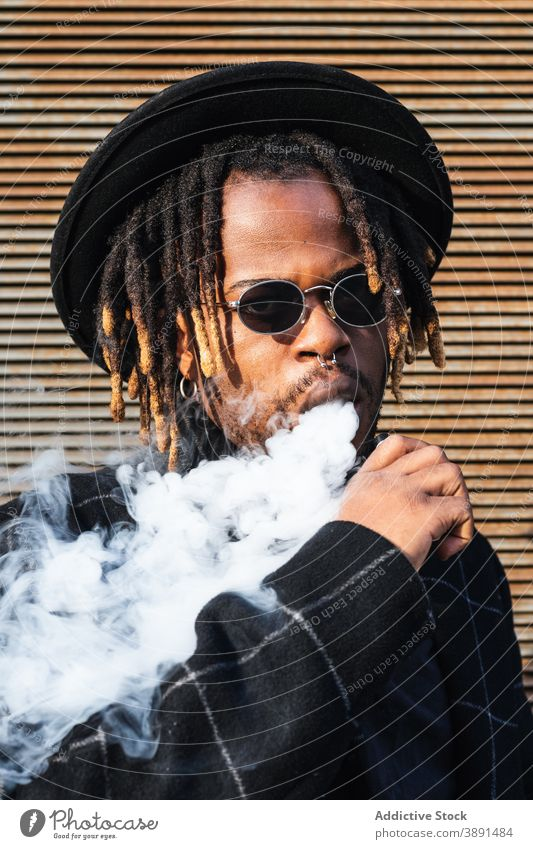 Trendy black man in hat smoking smoke exhale trendy cool lifestyle modern contemporary dreadlocks sunglasses african american ethnic personality street style