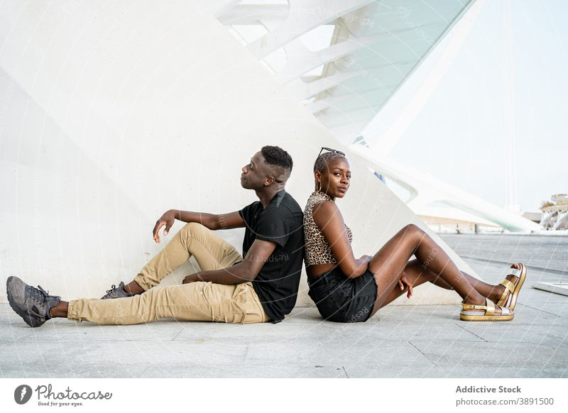 Black friends sitting back to back in city together street cool short hair appearance trendy young urban ethnic black african american rest style relax