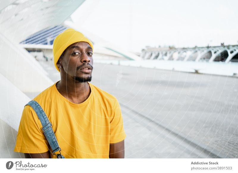 Black man standing in the street looking at camera trendy male ethnic black african american yellow outfit style modern bright appearance garment urban young