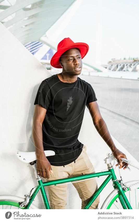 Stylish black man with bicycle in city urban style young bike modern trendy confident male ethnic african american street appearance hipster serious hat cool