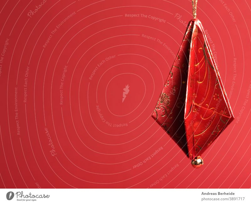Christmas tree decorations folded from beautiful red and gold decorative paper against a red background origami xmas homemade handmade christmas background