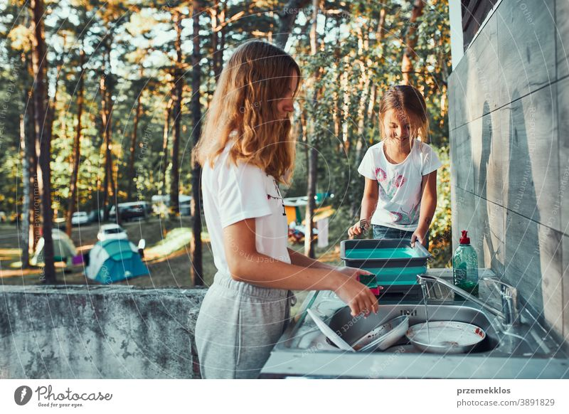 Teenager girl washing up the dishes pots and plates with help her younger sister in the outdoor kitchen during vacations on camping working together siblings