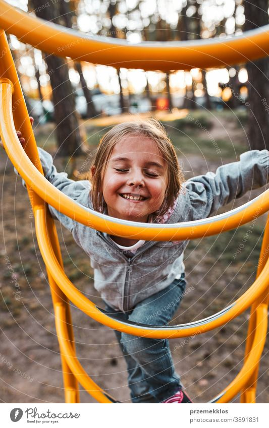 Playful happy girl preschooler playing on a playground climbing on monkey bars smiling with closed eyes positive joyful junior public place nursery outdoors