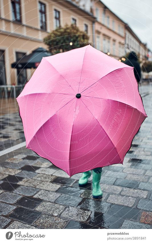 Child hiding behind big pink umbrella walking in a downtown on rainy gloomy autumn day raining outdoors little seasonal fall childhood beautiful weather outside