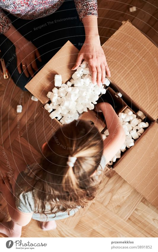 Woman unpacking a cardboard box parcel with help of her daughter view floor gift unboxing tape girl woman filler foam top open home wrapping opening shipping