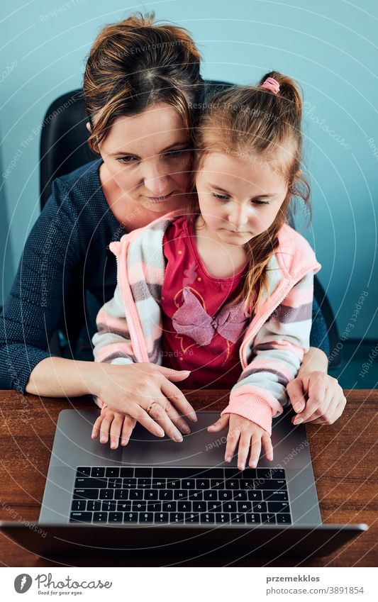 Little girl preschooler learning online solving puzzles playing educational games on laptop at home attention caucasian child childhood cute fun kid little