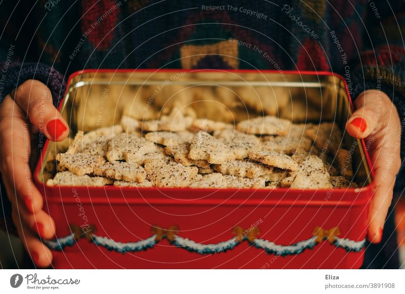 A woman holds a tin of homemade Christmas cookies in her hands Cookie Cookie jar Cookie tin fir trees biscuits Delicious Christmas & Advent Baked goods