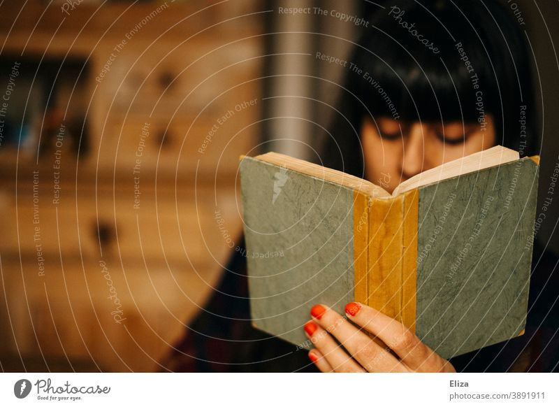 A woman reads a book Reading Book at home Woman Novel Old Reading matter hollowed browse books Diary Notebook Literature youthful Cozy by oneself