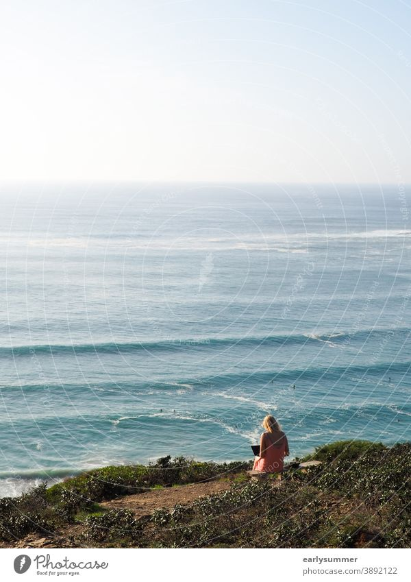 woman sitting on a cliff working at her laptop with view to the ocean and waves in portugal Office window Office work digital nomad Desk Change of job