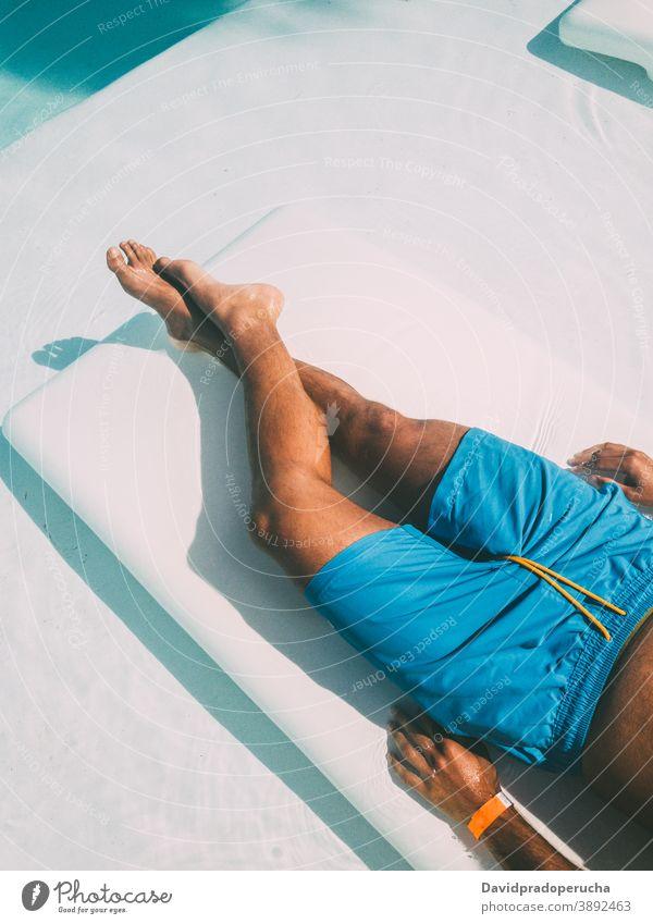 Crop man resting on lounger at poolside suntan deckchair sunbath vacation summer tourist relax lying traveler resort carefree hotel journey chill swimwear