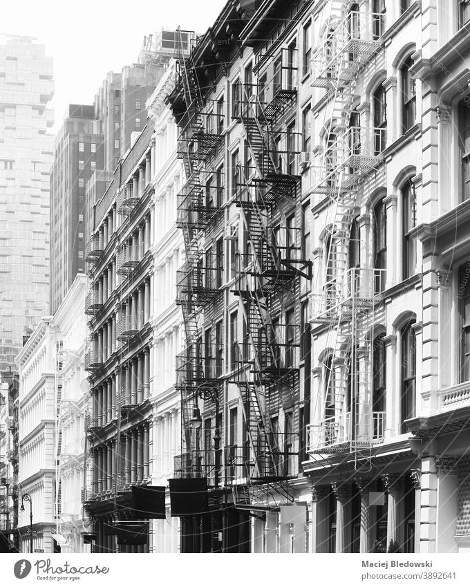 Black and white photo of buildings facades with fire escapes, New York, USA. city black and white house architecture NYC urban no people wall Manhattan