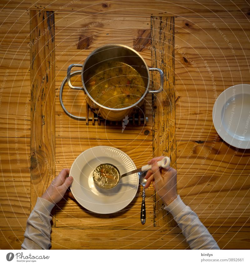 Pass out the soup, serve. Covered wooden table with soup pot, soup ladle, plate and spoons. Bird's eye view Soup Stew Plate Spoon Eating hands Arm Lunch