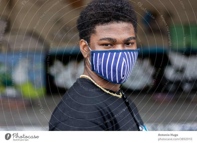 Portrait of young black boy with face mask. Graffiti wall background. virus gangster graffiti male african ethnic american crime expression grunge life rap