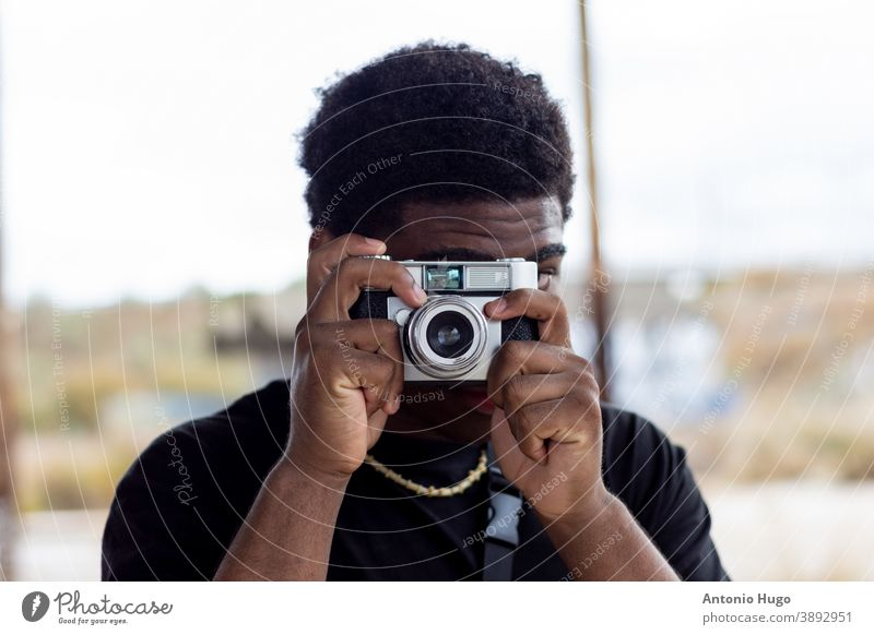 Portrait of black guy taking a picture with a vintage camera. photography photographer boy graffiti wall person youth male african ethnic gangster american