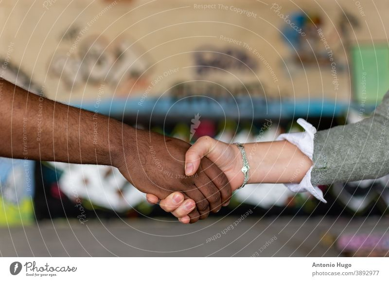 Black man and white woman holding hands. Union concept. Stop racism. Graffiti wall background. stop friendship african skin together agreement diversity human