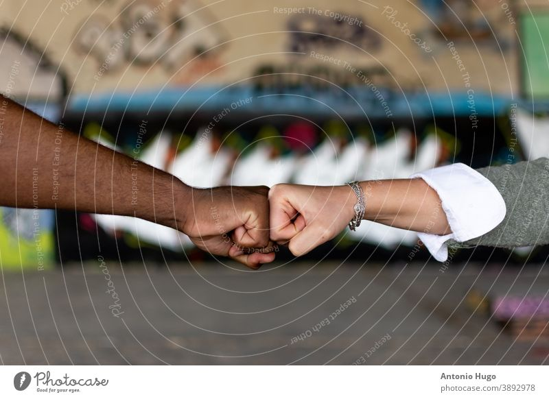 Black man and white woman clenching their fists. union concept. stop racism. Graffiti wall background. black holding hands friendship african skin together