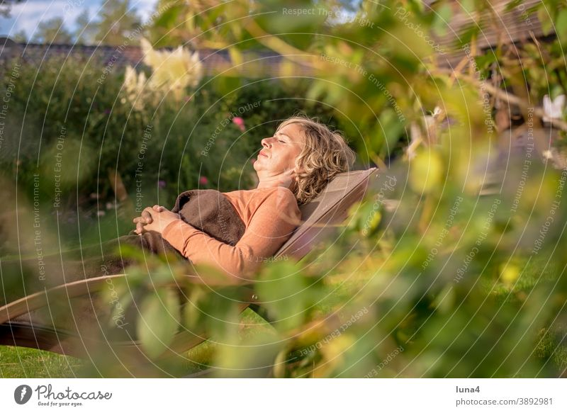 Woman lying in a deck chair Deckchair sunbathe Garden recover Sleep Rest relax To enjoy tranquillity Lie Autumn vacation holidays Sun Summer eyes closed