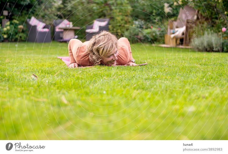 Woman doing push-ups in the garden gymnastics Push-ups Sports listless Force Fitness fun muscle workout tutorial Laughter cheerful foolish Mat Garden Meadow