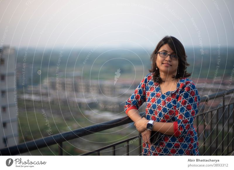 Portrait of an Indian Bengali brunette young woman in traditional wear standing on rooftop/balcony in the afternoon in urban background. Indian lifestyle adult
