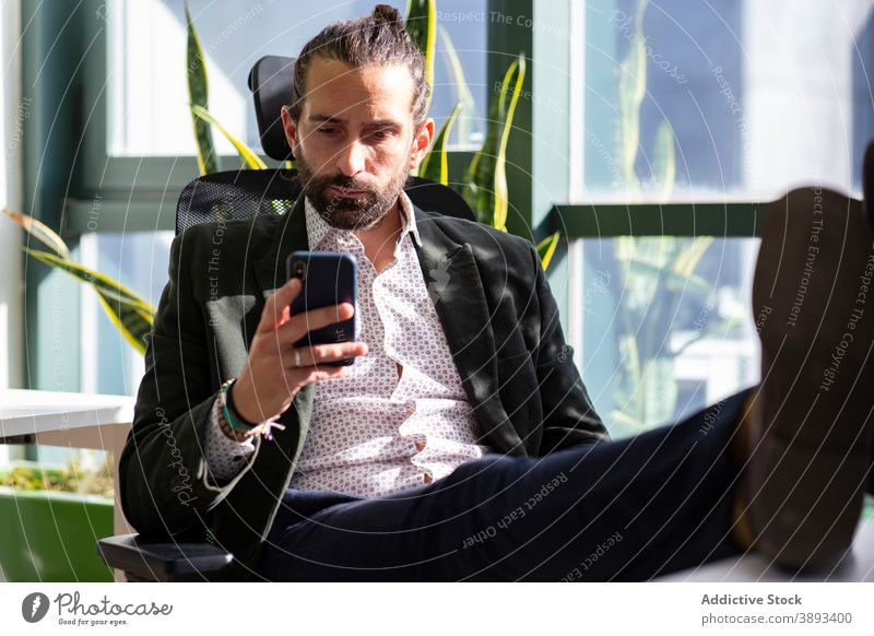 Serious businessman using smartphone in office read concentrate serious entrepreneur mobile break beard formal work workspace device gadget browsing connection