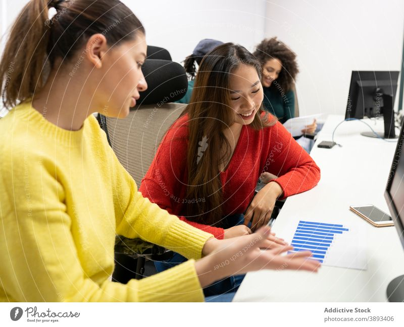Young female colleagues discussing charts in office work diagram casual positive women business together workplace coworker multiethnic multiracial diverse