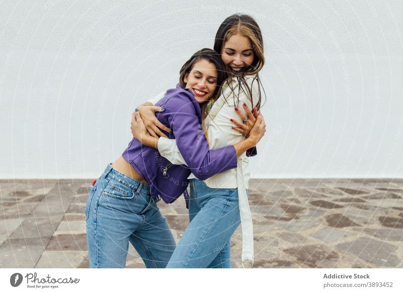 Happy girlfriends hugging on street embrace happy trendy young cheerful meeting urban together laugh female friendship relationship joy women glad optimist