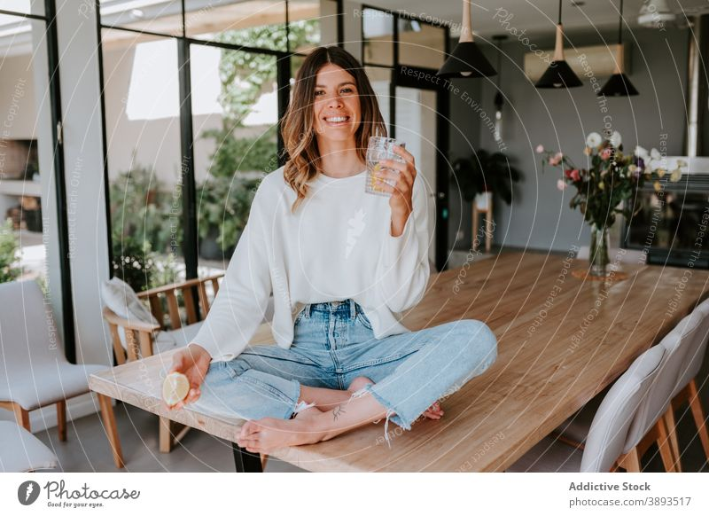 Smiling woman adding lemon juice in glass of water squeeze drink refreshment vitamin antioxidant beverage healthy female detox home natural citrus fruit organic