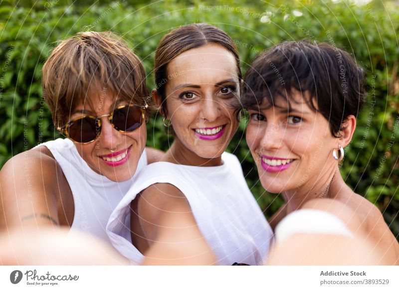Lovely friendly women taking selfie in city park self portrait friendship adult cheerful summer company together happy female smile enjoy hug delight group