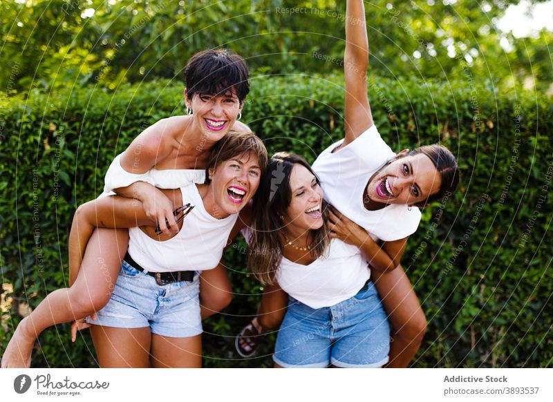 Company of cheerful women having fun in city piggyback friendship laugh humor bonding summer weekend together street delight girlfriend company glad style relax