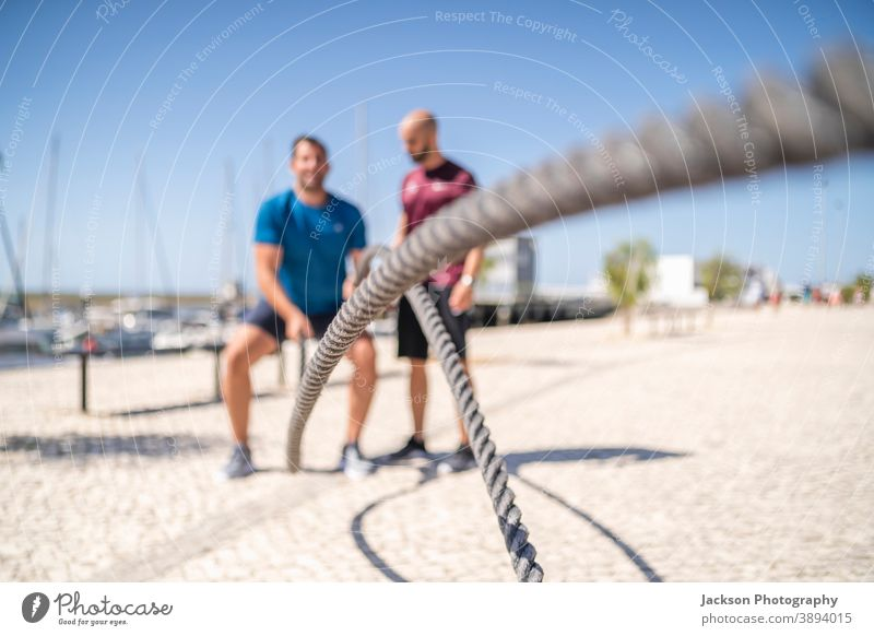 Battle ropes used outdoor by man and his personal trainer battle ropes exercise cross fit sportsman sweating men endurance sportswear heavy muscle cardio
