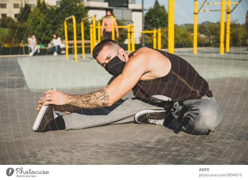 Young man with face mask stretching before calisthenics training sport warm up athlete coronavirus new normal pandemic facial mask muscles strength gymnastics