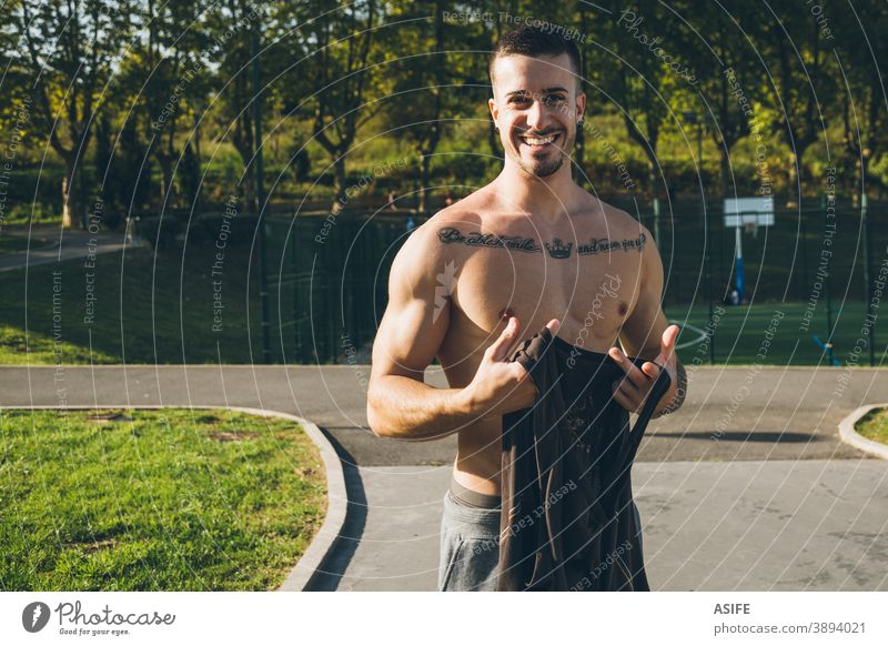 Young urban bodybuilder taking off the shirt before calisthenics training athlete man muscles strength gymnastics street happy funny smile portrait freestyle