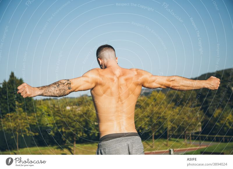 Young urban athlete warming up before calisthenics training sport warm up stretching man muscles back strength gymnastics street freestyle body shirtless