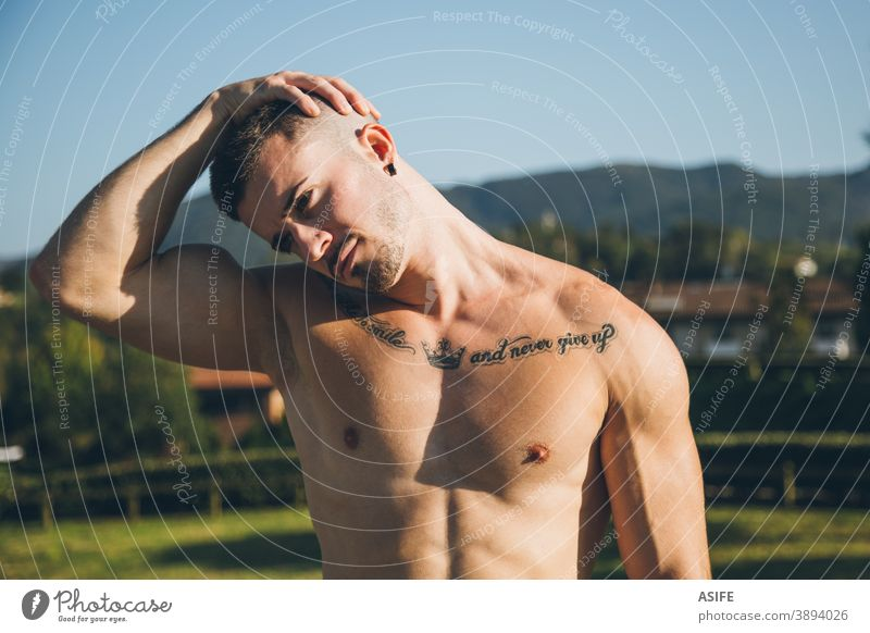 Young urban athlete stretching neck before calisthenics training sport warm up man muscles strength gymnastics street freestyle body shirtless outdoor aesthetic
