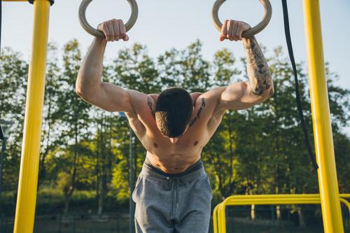 Athletic young man preparing and checking gymnastic rings calisthenics sport athlete muscles strength gymnastics street freestyle body shirtless outdoor