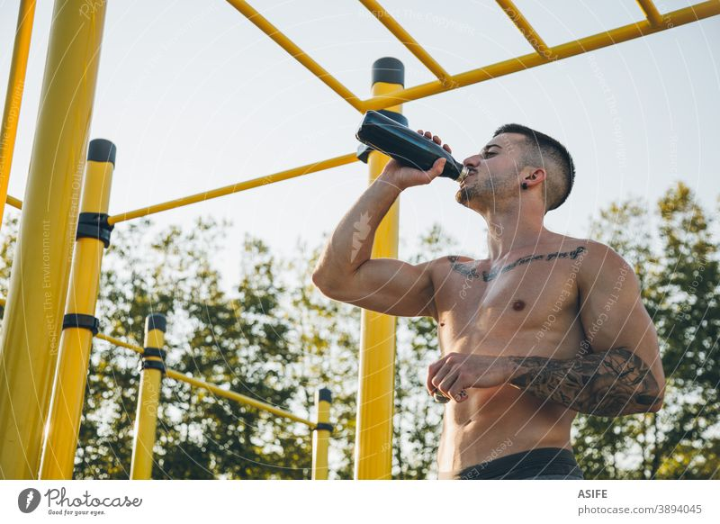 Young urban athlete drinking water at a calisthenics gym outdoor sport man bottle muscles strength gymnastics street freestyle body shirtless aesthetic tattoo