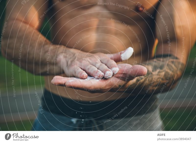 Young urban bodybuilder coating his hands with magnesium chalk for calisthenics training powder close up sport athlete man muscles strength gymnastics