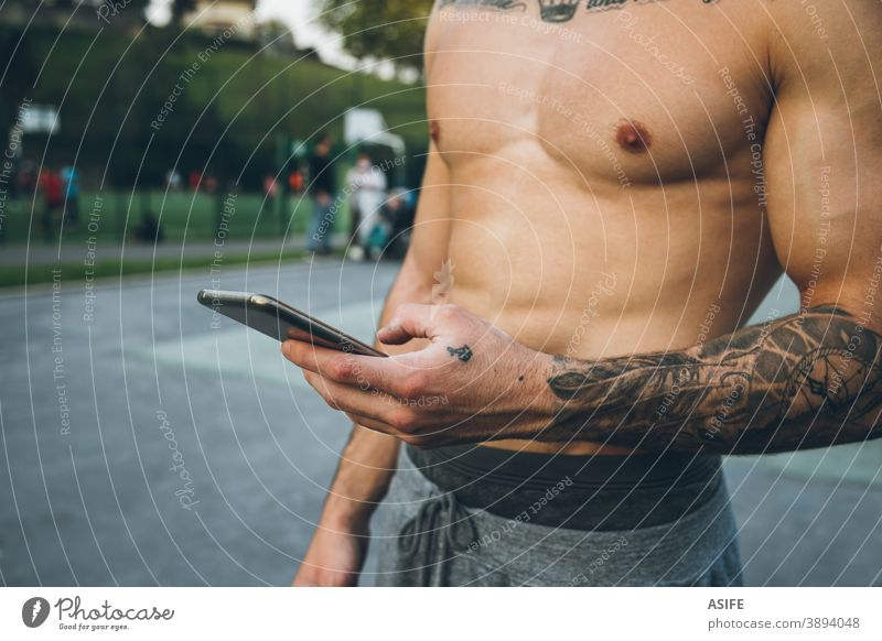 Young urban bodybuilder with tattoos using his smart phone during calisthenics training hands athlete man muscles mobile phone telephone arm sport strength