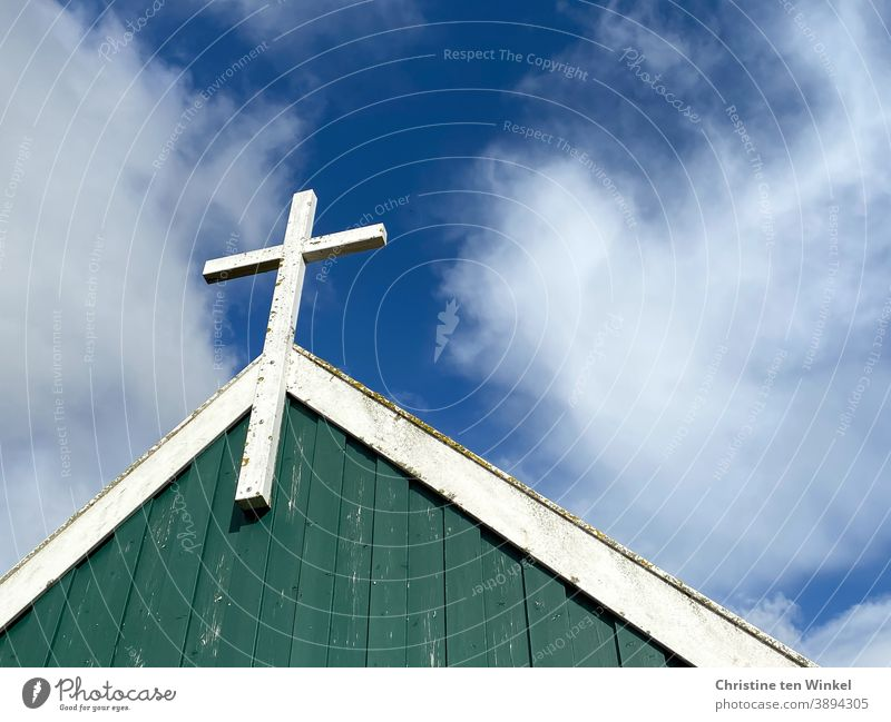 White wooden cross on the gable wall of a chapel, which is covered with green and white wood.  Everything is somewhat weathered. View from below against the blue cloudy sky. Spiekeroog I colour combination