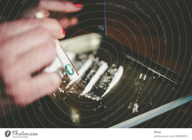 A woman consumes a white line in powder form with a rolled banknote through her nose drug use coke white powder Pull Nose Bank note Rolled Line Woman