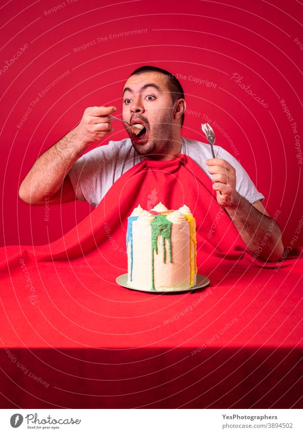 Man eating alone birthday cake. Greedy guy eating a huge cake. adult anniversary appetite big both hands buttercream cake celebrating celebration comfort food