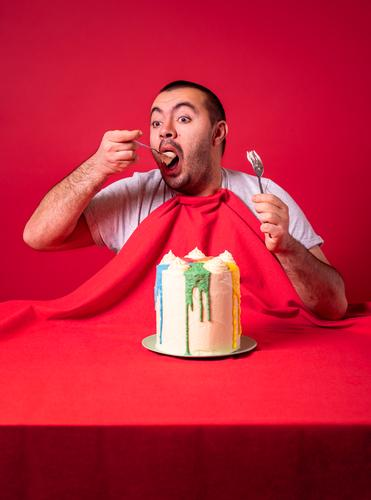 Man eating alone birthday cake. Greedy guy eating a huge cake. adult anniversary appetite big both hands buttercream cake celebrating celebration comfort food