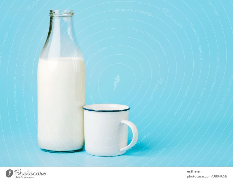 milk in a glass bottle and a white cup flow flowing cow fluid delicious healthy breakfast tasty yummy lunch nutrient protein diet still life kitchen ingredient