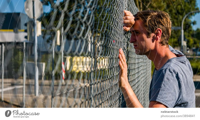 Sad Caucasian Man Leaning Head Against Fence portrait sad man sadness 1 person outdoor real life real person male profile side view state of mind emotion