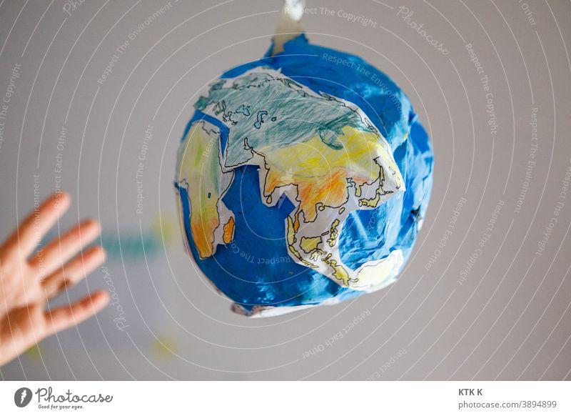 The world within reach; cardboard world earth Cardboard model earth papier mâché Model model building scale Fraud Hand Grasp ocean Continents Blue Water Earth