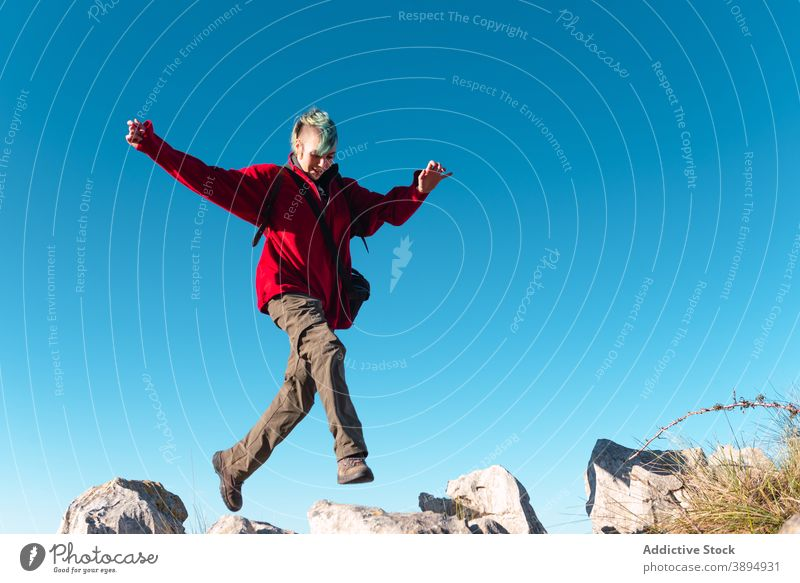 Cheerful hiker during trekking in mountains highland jump extreme adrenalin trail rock energy el mazuco asturias spain travel freedom terrain blue sky