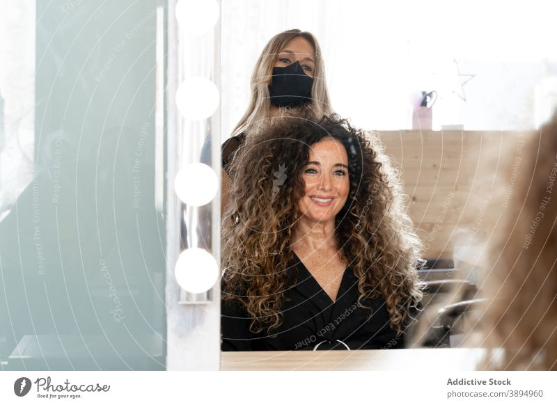 Hairdresser curling hair of woman hairdresser hairdo hairstyle women tong curly hair salon client beauty professional customer service procedure hairstylist