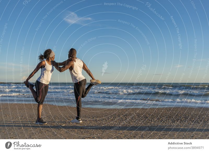 Black athletic couple training together on seashore workout warm up stretch relationship beach support ethnic black african american sportspeople athlete